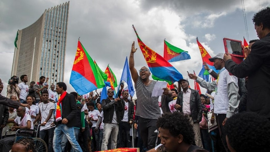 Eritrean refugees and dissidents, some holding Eritrean flags, demonstrate outside the headquarters of the African Union in Addis Ababa, Ethiopia, Thursday, June 23, 2016. Hundreds of Eritrean refugees and dissidents in Ethiopia have demonstrated against alleged human rights abuses committed by Eritrea's government, and supporting a new U.N. report that accuses it of crimes against humanity over the last 25 years. (AP Photo/Mulugeta Ayene)