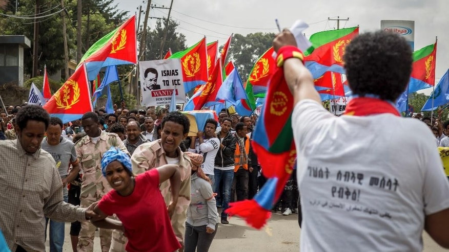 Eritrean refugees and dissidents, some holding Eritrean flags and some dressed as Eritrean military to illustrate beatings and torture, left, demonstrate outside the headquarters of the African Union in Addis Ababa, Ethiopia Thursday, June 23, 2016. Hundreds of Eritrean refugees and dissidents in Ethiopia have demonstrated against alleged human rights abuses committed by Eritrea's government, and supporting a new U.N. report that accuses it of crimes against humanity over the last 25 years. (AP Photo/Mulugeta Ayene)