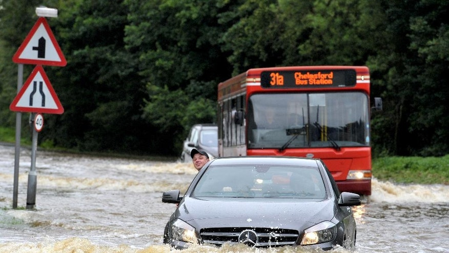 A man puts his head out of his vehicle as he drives along a flooded road in Writtle, England, as torrential downpours and flooding have swamped parts of London and the South East of England in the early hours of Thursday June 23, 2016.  The Fire Brigade have been inundated with emergency calls because of rising flood waters. (Nick Ansell / PA via AP) UNITED KINGDOM OUT - NO SALES - NO ARCHIVES