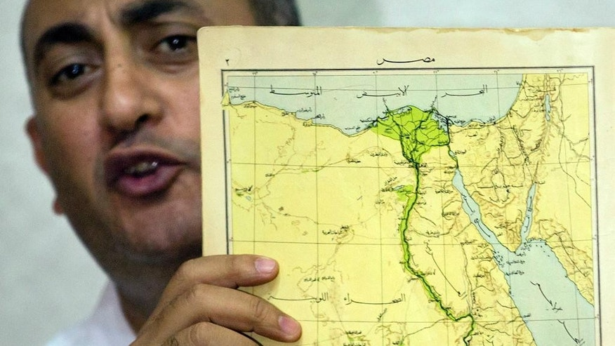 Egyptian lawyer and former presidential candidate Khaled Ali, displays an old map of Egypt including the two disputed Red Sea islands, during a press conference, in Cairo, Egypt, Wednesday, June 22, 2016. An Egyptian court has rejected as illegal a demarcation border agreement between Egypt and Saudi Arabia under which Cairo would surrender control over two Red Sea islands to Saudi Arabia. (AP Photo/Amr Nabil)