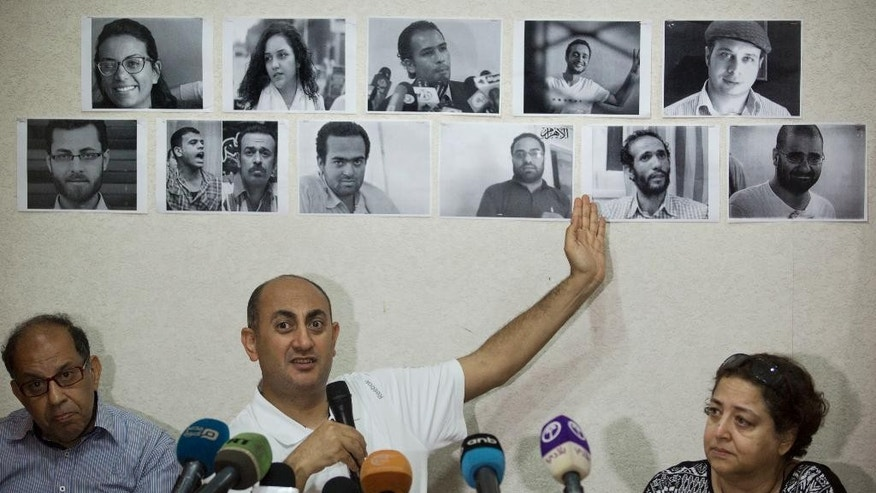 Egyptian lawyer and former presidential candidate Khaled Ali points to photos of jailed activists, who were arrested during protests over two disputed Red Sea islands, during a press conference, in Cairo, Egypt, Wednesday, June 22, 2016. An Egyptian court has rejected as illegal a demarcation border agreement between Egypt and Saudi Arabia under which Cairo would surrender control over two Red Sea islands to Saudi Arabia. (AP Photo/Amr Nabil)