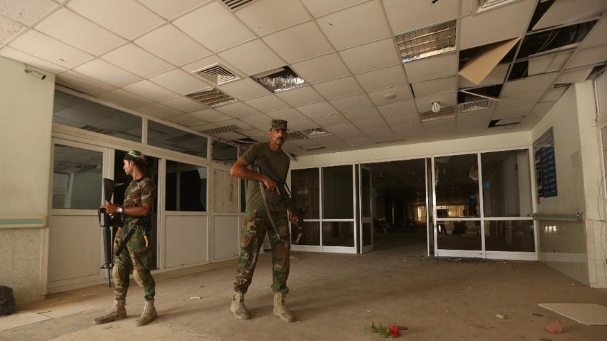 Iraqi soldiers inspect the hospital in Fallujah, Iraq, Wednesday, June 22, 2016. Pockets of Islamic State fighters continue to hold neighborhoods along the north and west of the city. (AP Photo/Hadi Mizban)