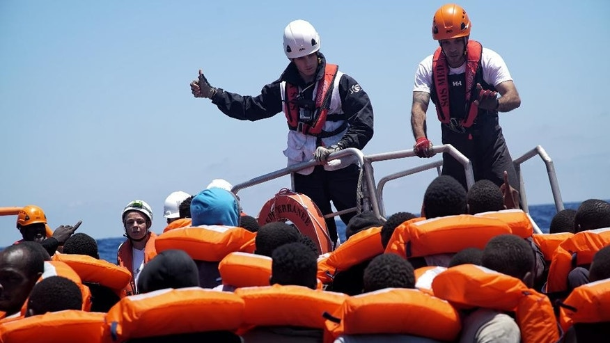 Rescue workers help distribute life jackets to migrants aboard a dinghy in the Mediterranean Sea being rescued by members of the aid group Medecins Sans Frontieres (MSF) and the rescue group SOS Mediterranee Rescuers of SOS Mediterranee, Thursday June 23, 2016.  The humanitarian groups distribute life jackets to the migrants in distress on the Mediterranean Sea before taking them aboard the 'Aquarius' vessel. (AP Photo/Bram Janssen)