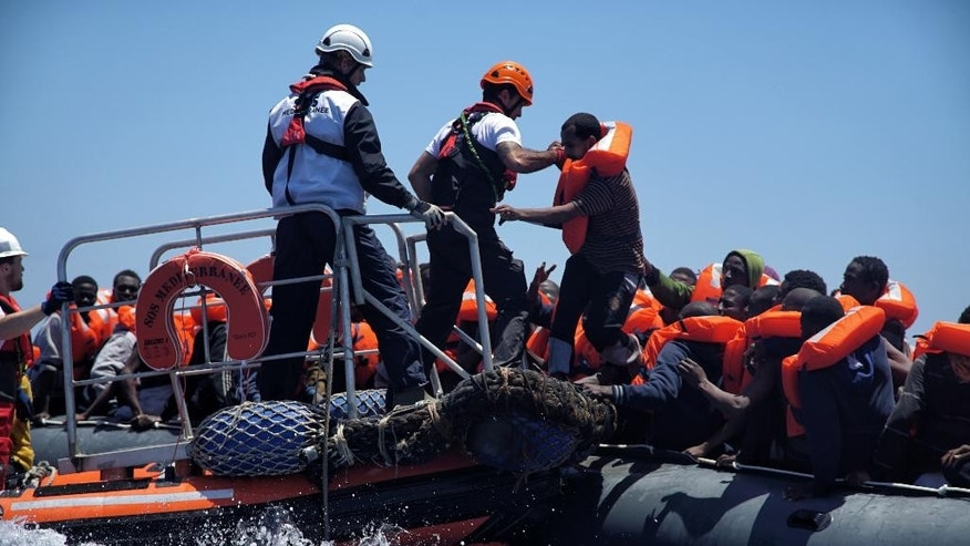 Rescue workers help migrants to disembark from a dinghy in the Mediterranean Sea, rescued by members of the aid group Medecins Sans Frontieres (MSF) and the rescue group SOS Mediterranee Rescuers of SOS Mediterranee, Thursday June 23, 2016.  The humanitarian groups distribute life jackets to the migrants in distress on the Mediterranean Sea before taking them aboard the 'Aquarius' vessel. (AP Photo/Bram Janssen)