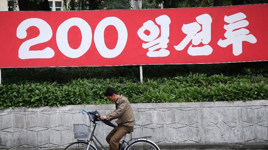"In this Wednesday, June 22, 2016, photo, a North Korean man cycles under a sign which reads ""200-day campaign,"" in Wonsan, North Korea. For the past few weeks, North Koreans across the nation have been mobilized for a 200-day ""speed campaign"" in line with their leader Kim Jong Un's vows to raise the nation's standard of living and energize his new five-year plan to develop the economy. (AP Photo/Wong Maye-E)"