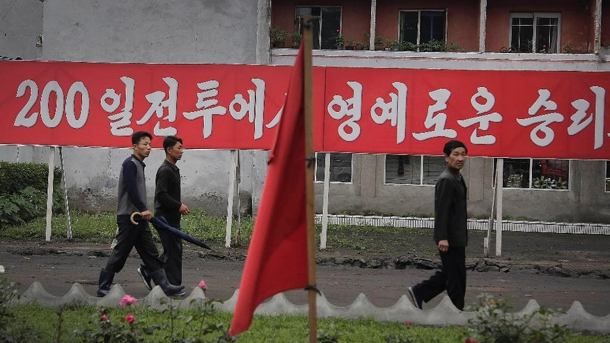 "In this Wednesday, June 22, 2016, photo, men pass a banner which reads ""Let us be honorable victors in the 200-day campaign"" in Wonsan, North Korea. For the past few weeks, North Koreans across the nation have been mobilized for a 200-day ""speed campaign"" in line with their leader Kim Jong Un's vows to raise the nation's standard of living and energize his new five-year plan to develop the economy. (AP Photo/Wong Maye-E)"