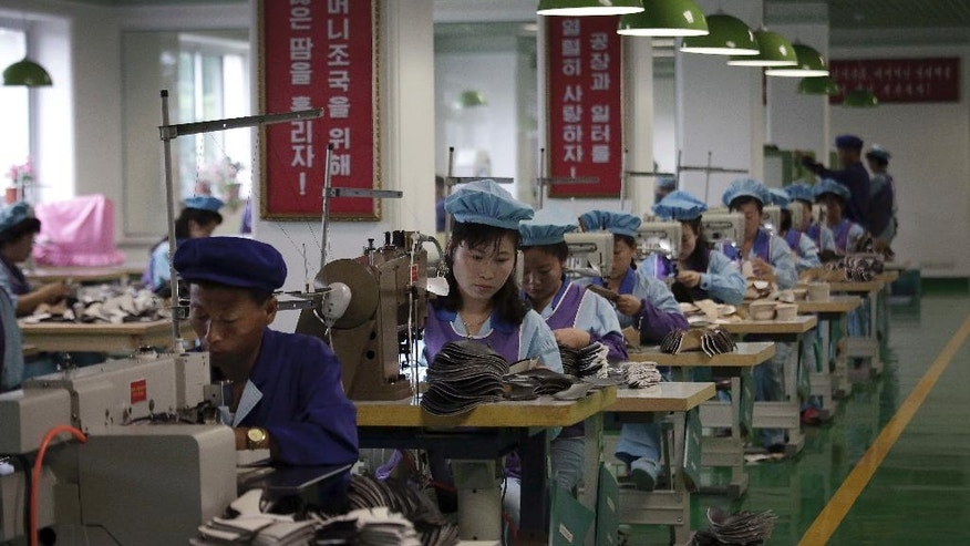 "In this Wednesday, June 22, 2016, photo, factory workers operate sewing machines at a shoe factory in Wonsan, North Korea. For the past few weeks, North Koreans across the nation have been mobilized for a 200-day ""speed campaign"" in line with their leader Kim Jong Un's vows to raise the nation's standard of living and energize his new five-year plan to develop the economy. At the direction of Kim Jong Un, who visited the factory last November, workers are now focusing on making lighter, better quality shoes and providing a wider variety to make North Korea's shoe production ""world class"" before the five-year plan ends. (AP Photo/Wong Maye-E)"