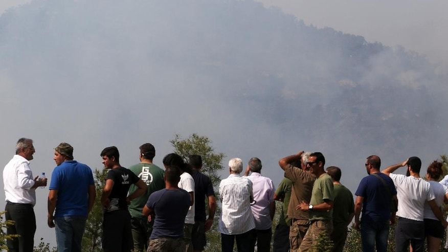 People watch a forest fire that continues to rage out of control for a third day in the mountainous areas southwest of Cyprus' capital Nicosia Tuesday, June 21, 2016. The fire has claimed the lives of two fire fighters. More planes from Italy and France are expected later Tuesday to join 16 other aircraft from Greece, Israel, Cyprus and British forces stationed on two military bases on the east Mediterranean island in battling the fire. (AP Photo/Philippos Christou )