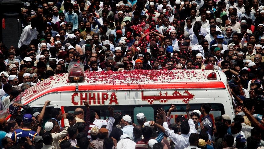 People throw rose petals on an ambulance carrying the body of Pakistani Sufi singer Amjad Sabri during his funeral in Karachi, Pakistan, Thursday, June 23, 2016. Thousands of mourners are attending the funeral of a well-known Pakistani Sufi singer who was shot dead in the port city of Karachi in an attack claimed by Islamic extremists. (AP Photo/Shakil Adil)