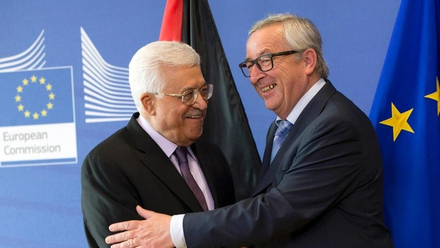 Palestinian President Mahmoud Abbas, left, is greeted by European Commission President Jean-Claude Juncker, right, prior to a meeting at EU headquarters in Brussels on Wednesday, June 22, 2016. Abbas is on a two-day trip to Brussels to meet with EU leaders. (AP Photo/Virginia Mayo)