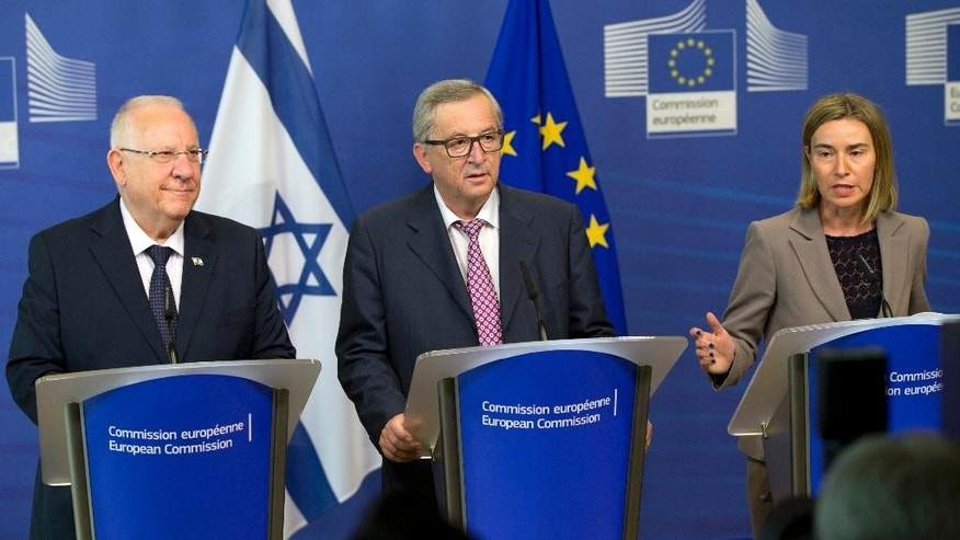 European Commission President Jean-Claude Juncker, center, and European Union High Representative Federica Mogherini, right, participate in a media conference with Israeli President Reuven Rivlin at EU headquarters in Brussels on Wednesday, June 22, 2016. (AP Photo/Virginia Mayo)