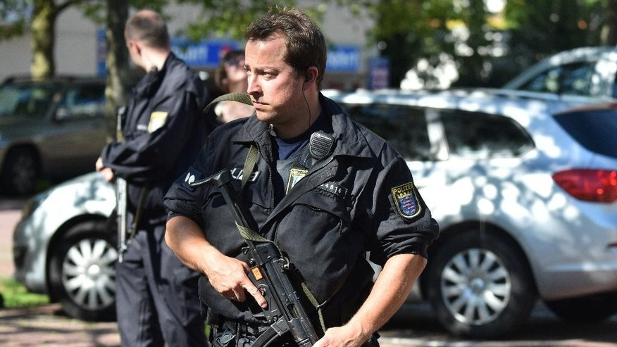 Police officers stand outside of a cinema in Viernheim near Mannheim, southern Germany, Thursday, June 23, 2016. A gunman was shot by police after he took hostages in the complex.  (Boris Roessler/dpa via AP)