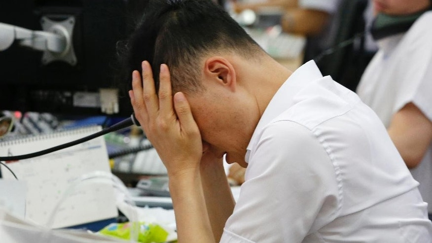 A currency trader rubs his eyes at the foreign exchange dealing room in Seoul, South Korea, Friday, June 24, 2016. Asian stock markets were volatile on Friday with Tokyo stocks and U.S. futures plunging as early vote results on whether Britain should stay in the European Union showed a tight race. (AP Photo/Lee Jin-man)