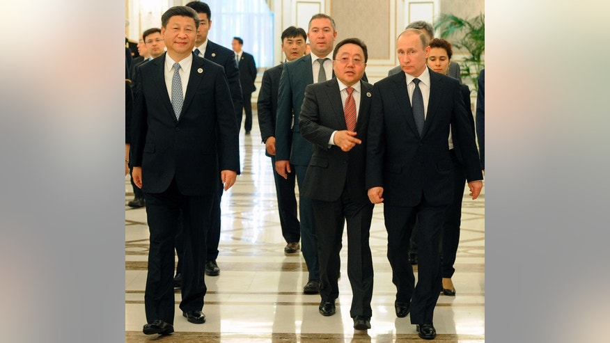 From left, Chinese President Xi Jinping, Mongolian President Tsakhiagiin Elbegdorj and Russian President Vladimir Putin walk during their meeting in Tashkent, Uzbekistan, where they attend the Shanghai Cooperation Organization summit on Thursday, June 23, 2016. (Mikhail Klimentyev/Sputnik, Kremlin Pool Photo via AP)