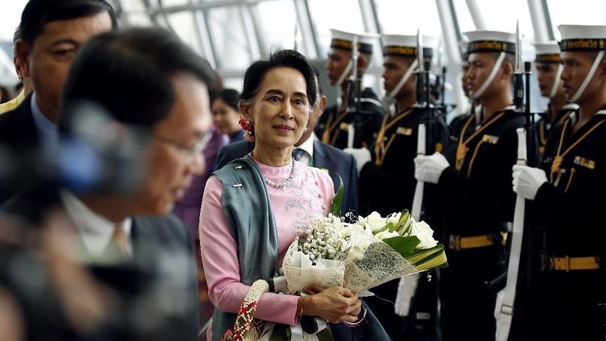 Myanmar Foreign Minister Aung San Suu Kyi, center, walks past a Thai honor guard as she arrives at the Suvarnabhumi Airport, Thursday, June 23, 2016, in Bangkok, Thailand. Suu Kyi is on an official three day visit to Thailand from June 23-25, 2016. (Narong Sangnak/Pool Photo via AP)