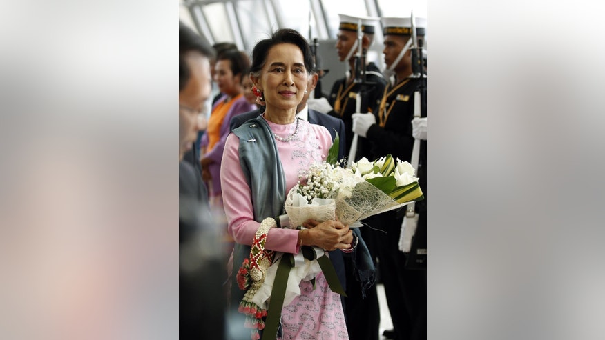 Myanmar Foreign Minister Aung San Suu Kyi is greeted with flowers as she arrives at the Suvarnabhumi Airport, Thursday, June 23, 2016, in Bangkok, Thailand. Suu Kyi is on an official three day visit to Thailand from June 23-25, 2016. (Narong Sangnak/Pool Photo via AP)