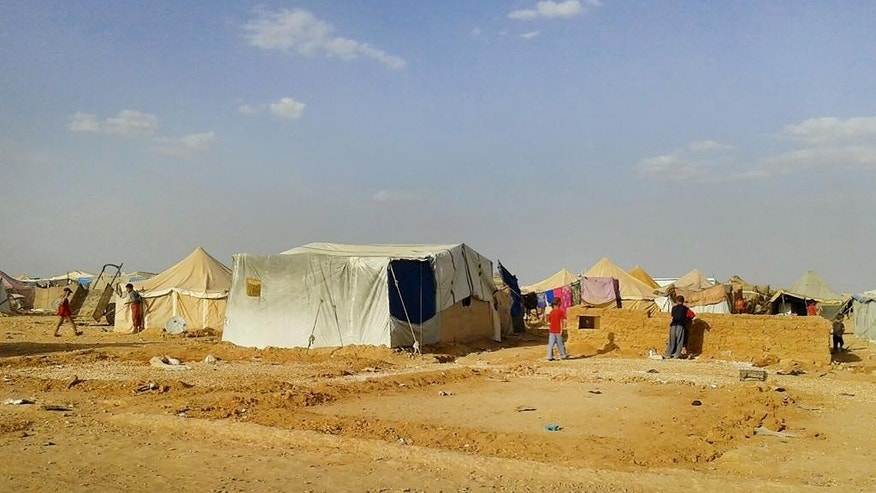 "In this Wednesday, June 22, 2016 photo, Syrians walk through the Ruqban refugee camp in Jordan's northeast border with Syria. Refugees stranded along the Jordanian border said that clean water is getting scarce in Ruqban after Jordan declared the area a ""closed military zone"" after a car bomb attack launched from Ruqban killed six Jordanian troops and wounded 14 at dawn Tuesday. Some 64,000 Syrians there depend on daily deliveries of food and water by international aid agencies based in Jordan. (AP Photo/Abu Adel)"