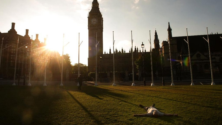 A man lays down on the green in Parliament Square as the sun rises behind the Houses of Parliament in London, Friday, June 24, 2016. Britain voted to leave the European Union after a bitterly divisive referendum campaign, according to tallies of official results Friday.  (Anthony Devlin/PA via AP) UNITED KINGDOM OUT, NO SALES, NO ARCHIVE