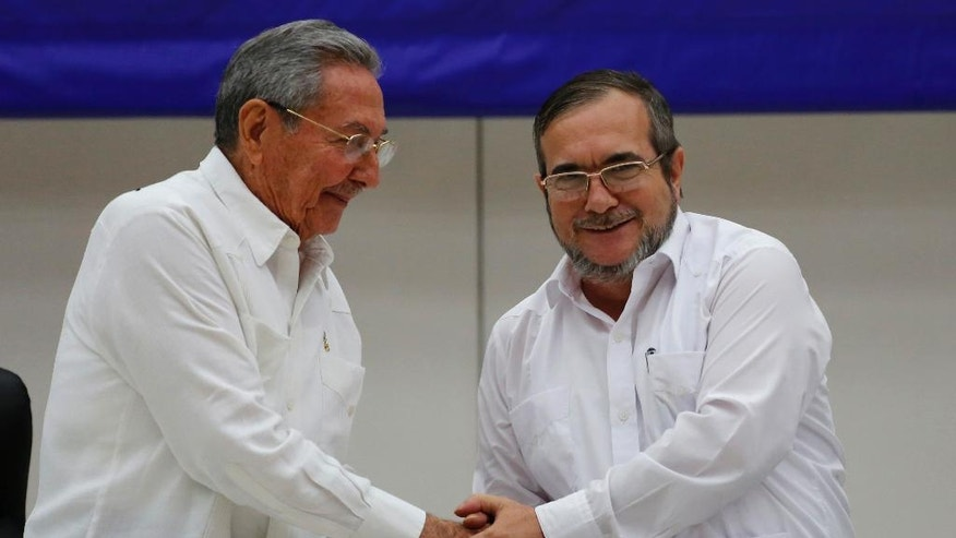 Cuba's President Raul Castro, left, shakes hands with Commander of the Revolutionary Armed Forces of Colombia or FARC, Rodrigo Londono, better known as Timochenko or Timoleon Jimenez, during a signing ceremony marking a cease-fire and rebel disarmament deal, in Havana, Cuba, Thursday, June 23, 2016. The deal moves Colombia closer to ending a 52-year war that has left more than 220,000 people dead. (AP Photo/Desmond Boylan)