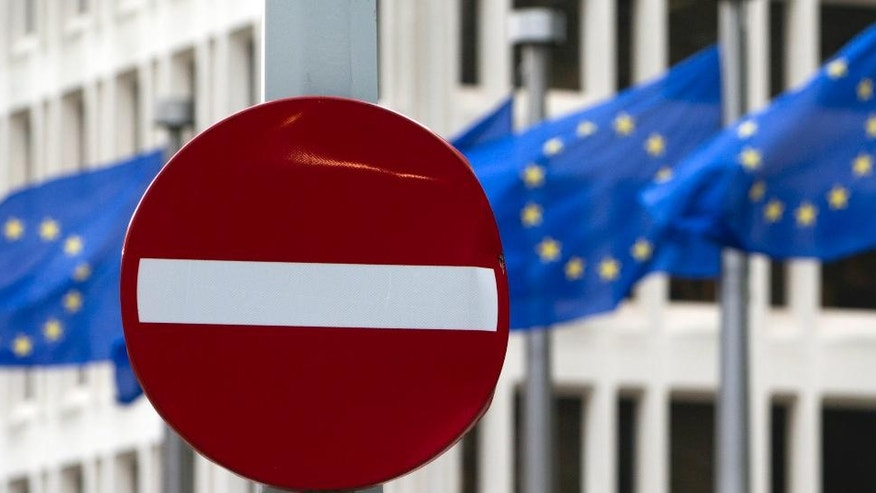 EU flags flutter in the wind in back of a no entry street sign in front of EU headquarters in Brussels on Friday, June 24, 2016. Voters in the United Kingdom voted in a referendum on Thursday to decide whether Britain remains part of the European Union or leaves the 28-nation bloc. Results will be known later on Friday. (AP Photo/Virginia Mayo)