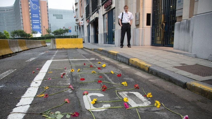A man looks down at flowers displayed in the words 'Please Stay' in front of the UK representation to the EU office in Brussels on Friday, June 24, 2016. Voters in the United Kingdom voted in a referendum on Thursday to decide whether Britain remains part of the European Union or leaves the 28-nation bloc. Results will be known later on Friday. (AP Photo/Virginia Mayo)