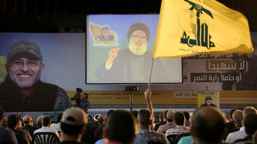 A Hezbollah supporter wave his group flag, as Hezbollah leader Sayyed Hassan Nasrallah, center, speaks via a video link during a ceremony marking the death of Hezbollah commander Mustafa Badreddine who was killed in in Damascus last month, in the southern suburb of Beirut, Lebanon, Friday, June 24, 2016. Nasrallah says the Lebanese Shiite militant group will send more fighters to Syria's Aleppo province, where pro-government forces are battling Syrian rebels on several fronts. (AP Photo/Hussein Malla)