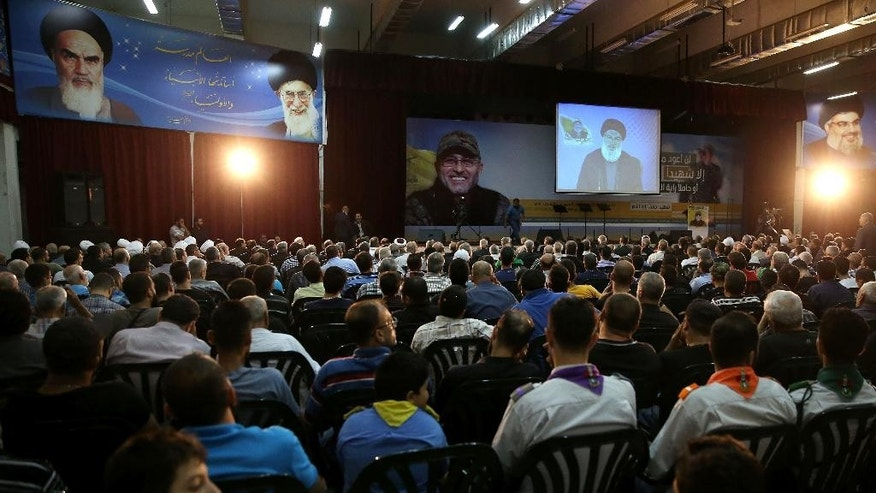 Hezbollah leader Sayyed Hassan Nasrallah, center, speaks via a video link during a ceremony marking the death of Hezbollah commander Mustafa Badreddine who was killed in in Damascus last month, in the southern suburb of Beirut, Lebanon, Friday, June 24, 2016. Nasrallah says the Lebanese Shiite militant group will send more fighters to Syria's Aleppo province, where pro-government forces are battling Syrian rebels on several fronts. (AP Photo/Hussein Malla)