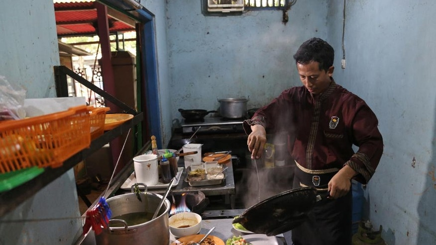 """In this Monday, May 16, 2016 photo, Mahmudi Haryono, 40, who is also known by his militant alias """"Yusuf Adirama"""" cooks in the kitchen of his restaurant in Solo, Central Java, Indonesia. Haryono who also runs a car-hire business and a laundry service is one of the poster boys for the transformation of a jihadist into a productive member of society, a success owed to the work of a private group with limited funds that reaches only a minority of people. (AP Photo/Achmad Ibrahim)"""
