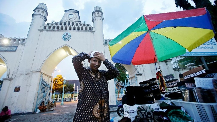 """In this Monday, May 16, 2016 photo, Mahmudi Haryono, 40, who is also known by his militant alias """"Yusuf Adirama"""" tries on a prayer cap as he arrives at a mosque for an evening prayer in Solo, Central Java, Indonesia. Haryono who also runs a restaurant, car-hire business and a laundry service is one of the poster boys for the transformation of a jihadist into a productive member of society, a success owed to the work of a private group with limited funds that reaches only a minority of people. (AP Photo/Achmad Ibrahim)"""