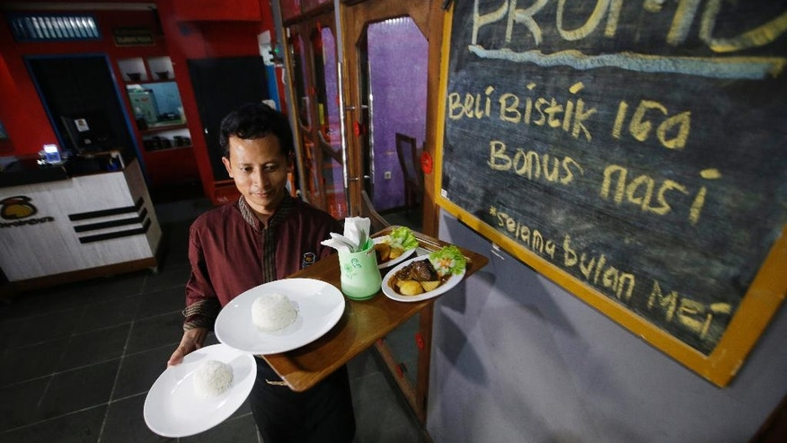 """In this Monday, May 16, 2016 photo, Mahmudi Haryono, 40, who is also known by his militant alias """"Yusuf Adirama"""" carries a tray of food for customers at his restaurant in Solo, Central Java, Indonesia. Haryono who also runs a car hire business and a laundry service is one of the poster boys for the transformation of a jihadist into a productive member of society, a success owed to the work of a private group with limited funds that reaches only a minority of people. Writings on the board say """"May Promo, buy a beef ribs and get free rice"""". (AP Photo/Achmad Ibrahim)"""