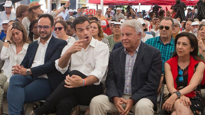 Spanish Socialist leader Pedro Sanchez, center, gestures next to former Spanish Premier Felipe Gonzalez, center right, during a election rally on the last day of campaigning, in Madrid, Spain, Friday June 24, 2016. Spaniards are voting in a general election Sunday, just six months after a last unsuccessful attempt to pick a new government. (AP Photo/Paul White)