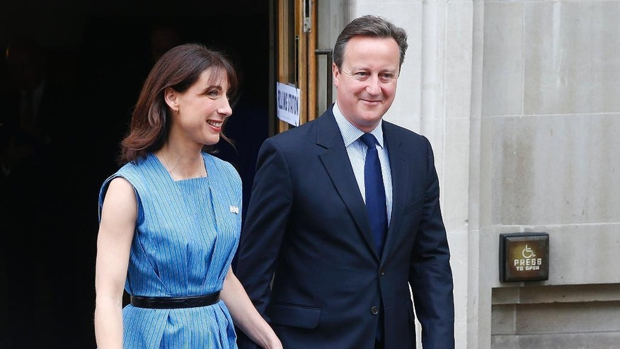Britain's Prime Minister David Cameron and his wife Samantha smiles as they leave after voting in the EU referendum in London, Thursday June 23, 2016. Polls opened in Britain Thursday for a referendum on whether the country should quit the European Union bloc of which it has been a member for 43 years. (AP Photo/Alastair Grant)