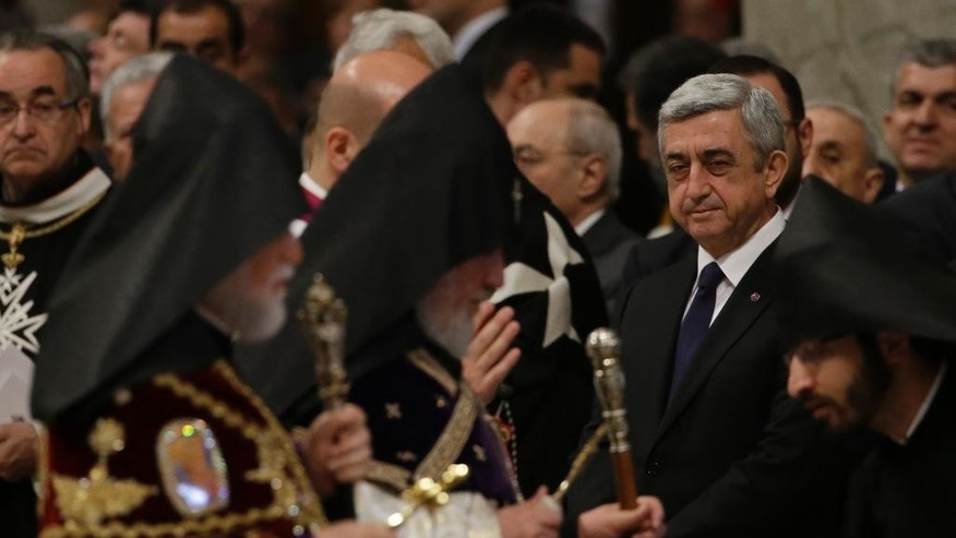 FILE - In this  Sunday, April 12, 2015 file photo, the head of Armenia's Orthodox Church Karekin II, second from left, flanked by Catholicos Aram I, left, walks past Armenian President Serzh Sargsyan, center, during an Armenian-Rite Mass celebrated by Pope Francis to commemorate the 100th anniversary of the Armenian Genocide, in St. Peter's Basilica, at the Vatican. Pope Francis is making his first foray into the former Soviet Union with a weekend visit to Armenia, a year after he riled Turkey by declaring the Ottoman-era slaughter of Armenians genocide and amid fresh tensions with rival Azerbaijan. (AP Photo/Gregorio Borgia, File)
