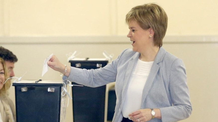 Scotland's First Minister, Nicola Sturgeon, casts her vote in Glasgow, Scotland, Thursday June 23, 2016, as voters head to the polls across the United Kingdom in a historic referendum on whether the UK should remain a member of the European Union or leave. (Jane Barlow/PA via AP)  UNITED KINGDOM OUT
