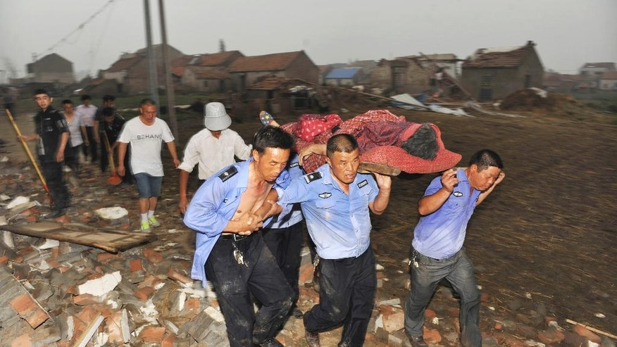 Residents carry an injured woman rescued from a collapsed house in Funing county in Yancheng city of eastern China's Jiangsu Province on Thursday June 23, 2016.  A powerful tornado hit Thursday, with reports of dozens killed and large numbers of buildings destroyed in the eastern Chinese province of Jiangsu,  according to state media.  (Chinatopix Via AP) CHINA OUT