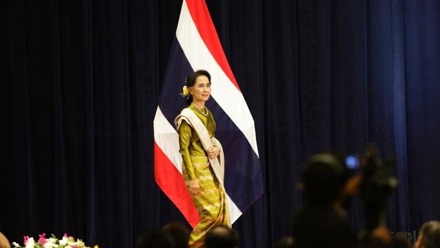 Myanmar's Foreign Minister Aung San Suu Kyi walks on to the stage before delivering a speech at the Foreign Ministry in Bangkok, Thailand, Friday, June 24, 2016. Suu Kyi is on an official three-day visit to Thailand from June 23-25. (AP Photo/Sakchai Lalit)