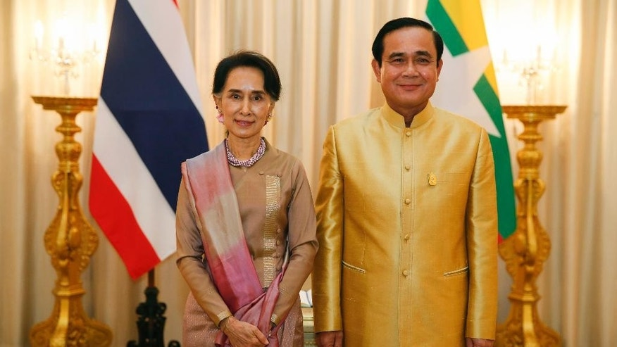 Thai Prime Minister Prayuth Chan-ocha, right, and Myanmar's Foreign Minister and State Counselor Aung San Suu Kyi pose for photographers during their meeting at government house in Bangkok, Thailand, June 24, 2016. Myanmar's de facto leader  Suu Kyi met with Prayuth to sign memorandums of understanding over the processing of and the treatment of Myanmar migrant workers in Thailand, who labor in menial jobs and often in exploitative conditions. (Jorge Silva/Pool Photo via AP)