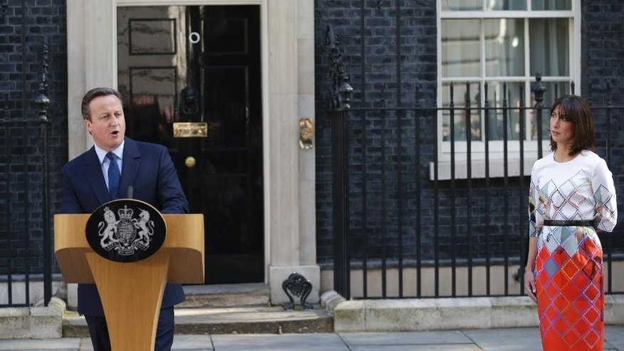 Britain's Prime Minister David Cameron speaks outside 10 Downing Street, London as his wife Samantha looks on Friday, June 24, 2016. Cameron says he will resign by the time of party conference in the fall after  Britain voted to leave the European Union after a bitterly divisive referendum campaign, according to tallies of official results Friday. (Daniel Leal-Olivas/PA via AP) UNITED KINGDOM OUT, NO SALES, NO ARCHIVE