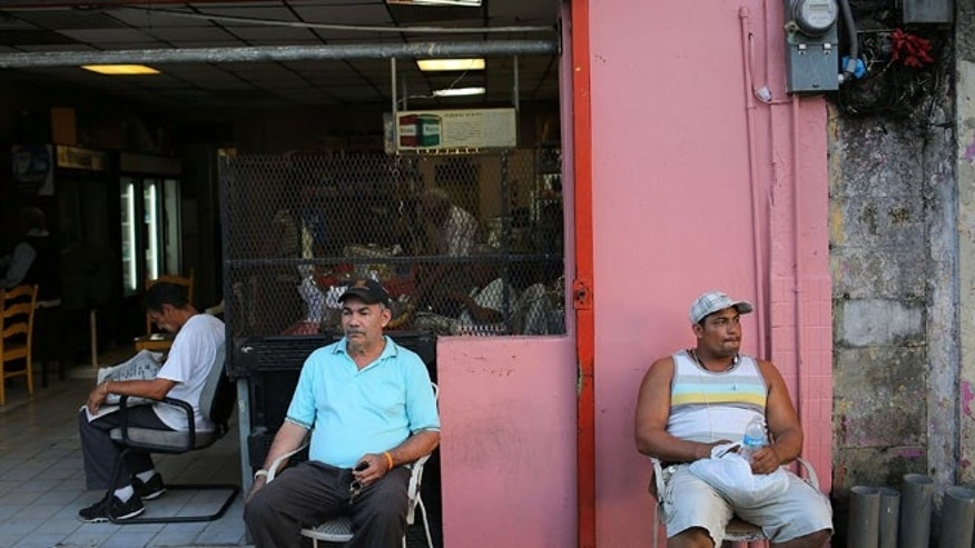 SAN JUAN, PUERTO RICO - JUNE 30:  Valerio Ginairs (L) and Ricardo de la Cruz relax outside a bar a day after Puerto Rican Governor Alejandro Garcia Padilla gave a televised speech regarding the governments $72 billion debt on June 30, 2015 in San Juan, Puerto Rico.  The governor said in his speech that the people will have to sacrifice and share in the responsibilities for pulling the island out of debt.  (Photo by Joe Raedle/Getty Images)