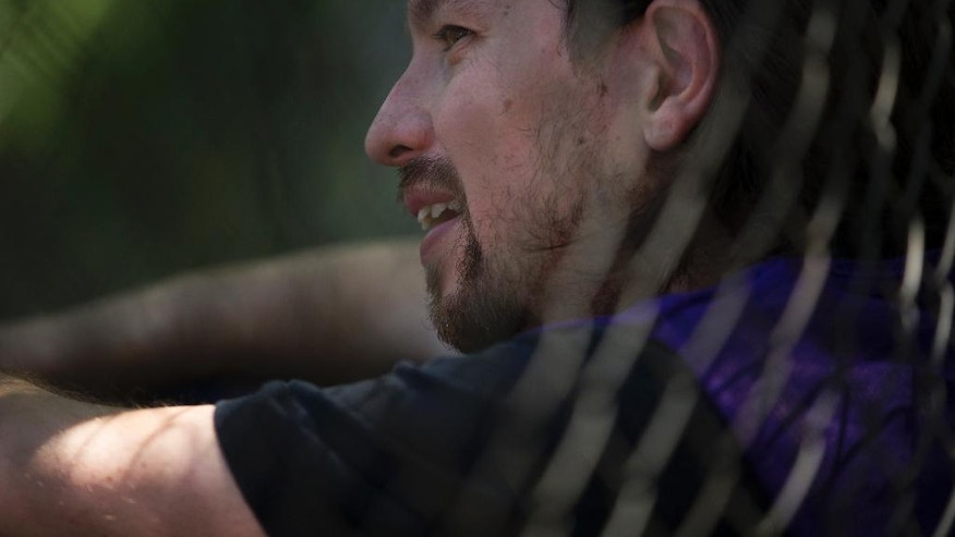 Spain's Unidos Podemos coalition party leader Pablo Iglesias rests leaning on a net after a basketball match with some friends at the Complutense University of Madrid sports campus in Madrid, Saturday, June 25, 2016. Spaniards are voting in a general election Sunday 26, just six months after a last unsuccessful attempt to pick a new government. (AP Photo/Francisco Seco)