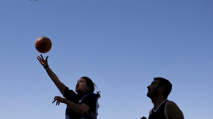 Spain's Unidos Podemos coalition party leader Pablo Iglesias, left, goes with the ball to the basket during a basketball match with some friends at the Complutense University of Madrid sports campus in Madrid, Saturday, June 25, 2016. Spaniards are voting in a general election Sunday 26, just six months after a last unsuccessful attempt to pick a new government. (AP Photo/Francisco Seco)