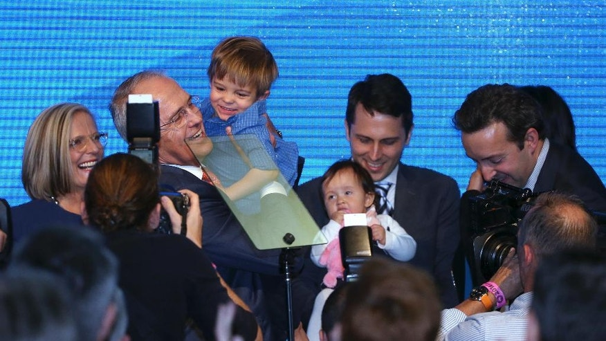 Australian Prime Minister Malcolm Turnbull, second from left, holds his grandson, Jack, as his family gather on stage after his Liberal Party election campaign launch speech in Sydney, Sunday, June 26, 2016. A national election will be held July 2. (AP Photo/Rick Rycroft)