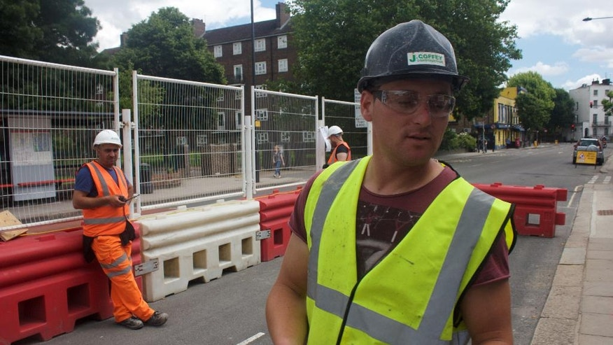 In this photo taken on Friday, June 24, 2016, Iosif Achim, a 32-year-old Romanian logistics manager, right, stands at a construction site while being interviewed in London. Many of the hundreds of thousands of workers in Britain who hail from other EU countries are struggling with uncertainty about their future in Britain after the nation voted to leave the 28-member bloc. (AP Photo, Pawel Kuczynski)