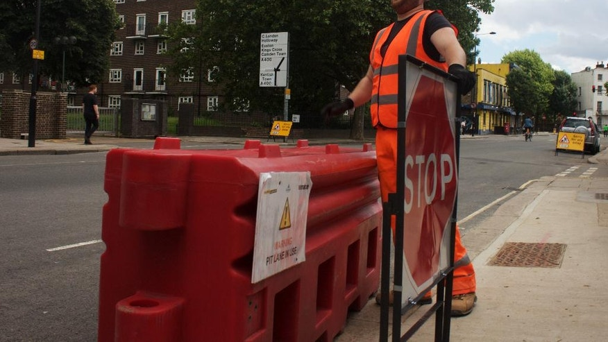 In this photo taken on Friday, June 24, 2016, Gabriel Ionut, a 24-year-old Romanian who works as a traffic marshal, stands by a signal at a construction site in London. Ionut is in the minority of the hundreds of thousands of foreign European workers who welcomed the British decision to leave the European Union as the majority of them are struggling with uncertainty about their future in Britain. (AP Photo, Pawel Kuczynski)