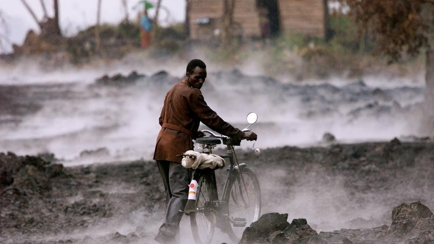 FILE-In this file photo taken Thursday, Jan. 24, 2002, a Congolese man pushes his bicycle across lava rock covered in steam, after a rain storm in the eastern Congolese town of Goma. Traumatized farmers are slowly returning to fields decimated by the 2002 eruption of Mount Nyiragongo in eastern Congo. Flowing lava flattened more than 30 percent of the city of Goma, 20 kilometers away. (AP Photo/Karel Prinsloo,File)