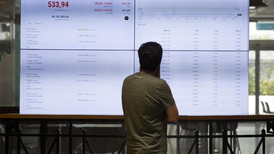 """A man looks at an index board at the reception hall of the Stock Exchange in Athens, Friday, June. 24, 2016. Greece's prime minister says the British referendum dealt a severe blow to European unification, and should force a shift toward more """"democratic"""" practices within the European Union. Athens stocks tumbled 14 percent Friday.(AP Photo/Petros Giannakouris)"""
