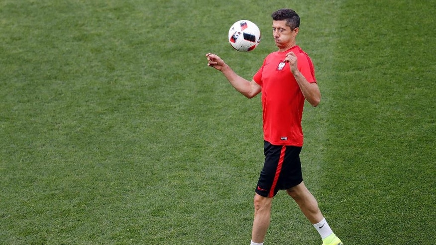 Poland's Robert Lewandowski stops the ball during a training session at the Geoffroy Guichard stadium in Saint-Etienne, France, Friday, June 24, 2016. Poland will face Switzerland in a Euro 2016 round of sixteen soccer match in Saint-Etienne on Saturday, June 25, 2016. (AP Photo/Michael Sohn)