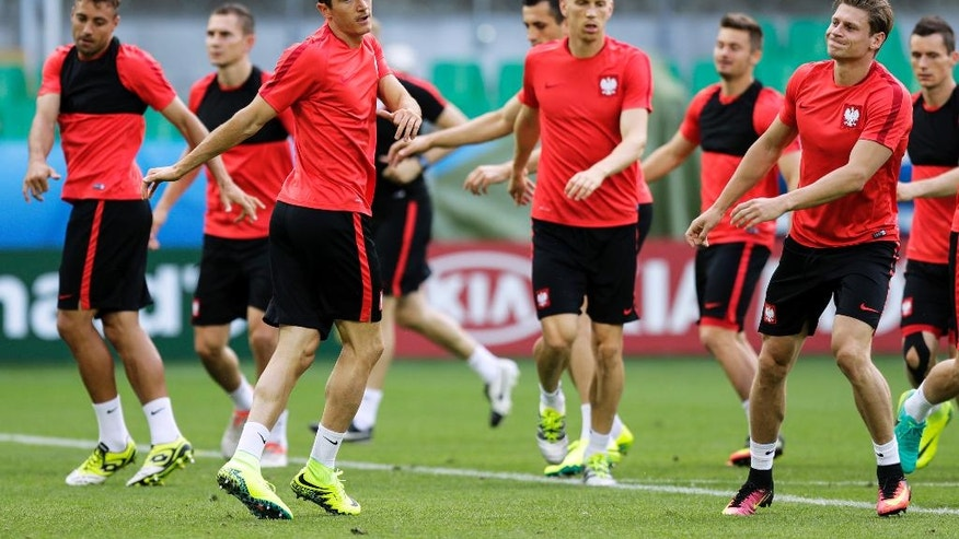 Poland's Robbert Lewandowski, third from left, attends a training session at the Geoffroy Guichard stadium in Saint-Etienne, France, Friday, June 24, 2016. Poland will face Switzerland in a Euro 2016 round of sixteen soccer match in Saint-Etienne on Saturday, June 25, 2016. (AP Photo/Pavel Golovkin)