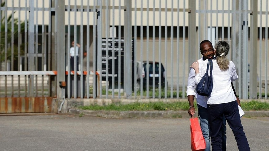 Rudy Guede, left, is greeted by an unidentified person as he leaves the Viterbo's penitentiary, Italy, Saturday, June 25, 2016. Guede, who was convicted to 16-year in prison for the 2007 murder of  the British student Meredith Kercher in Perugia, left Saturday the penitentiary for a temporary release of thirty-six hours to spend in a volunteer centre for prisoner assistance in the city of Viterbo. (AP Photo/Gregorio Borgia)