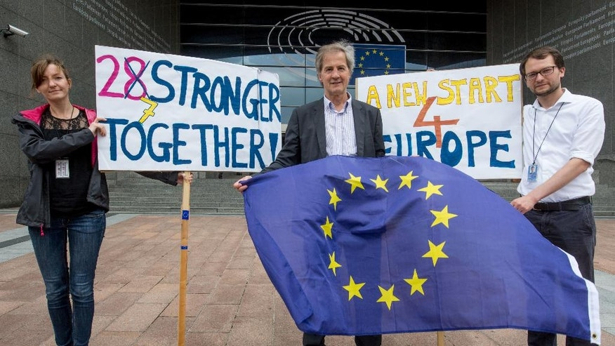 German Member of Parliament, Jo Leinen, center, holds an EU flag outside European Parliament in Brussels on Friday, June 24, 2016. Top European Union officials were hunkering down in Brussels Friday to try to work out what to do next after the shock decision by British voters to leave the 28-nation bloc. (AP Photo/Olivier Matthys)